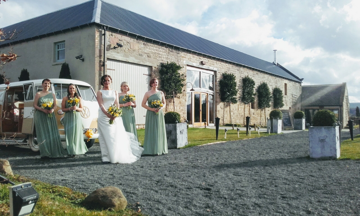 Sunny photo of bride and bridesmaids outside of Healey Barn