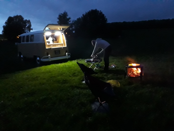 Julie cooking at the back of VW Campervan with lights on and fire glowing