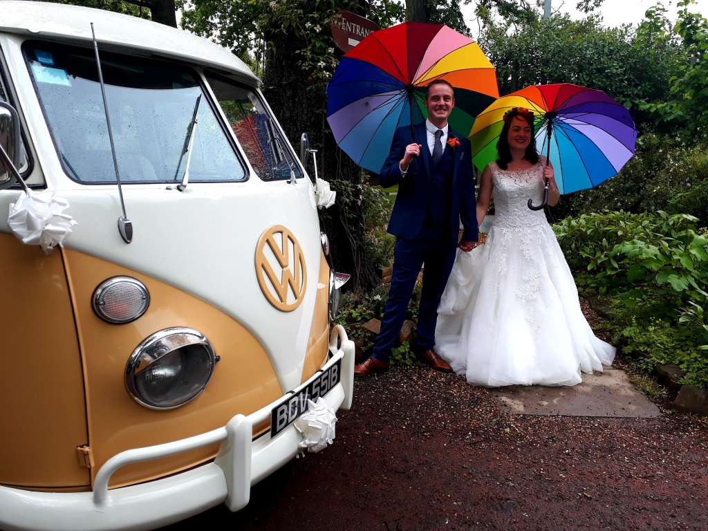 Campervan outside the Parlour at Blagdon entrance, bride and groom holding colourful Umbrella's
