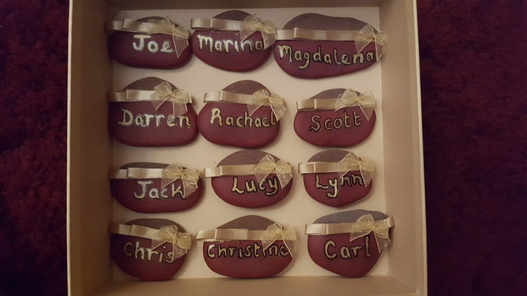 Hand painted red smooth pebbles with wedding guest names, bows and ribbons in gold