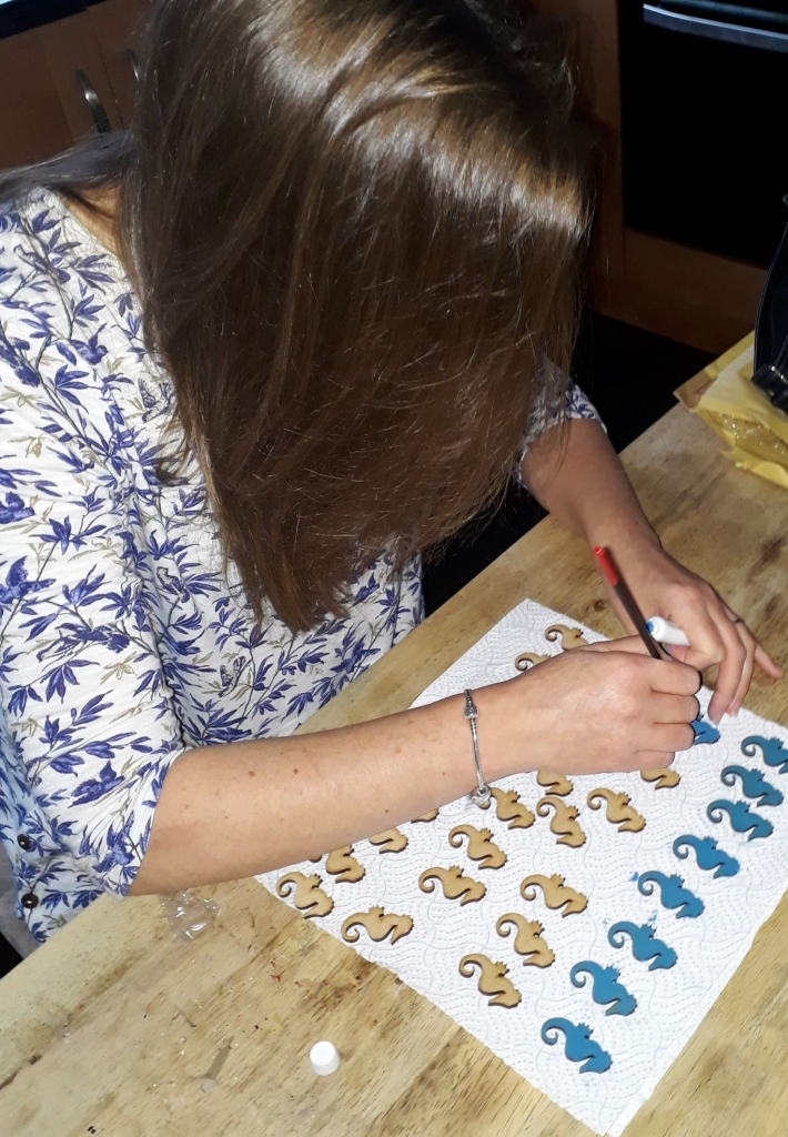 Hand painting wooden seahorses with blue paint